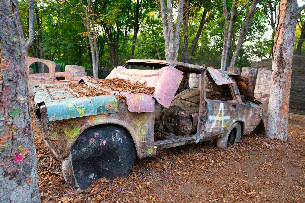 An old rusty and abandoned car at a paintball base behind which players excited by the game are hiding